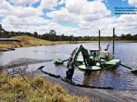 Amphibious Multipurpose Watermaster Recovering coal fines from settling ponds by suction dredging the wet coal ash into dewatering bags, Australia.