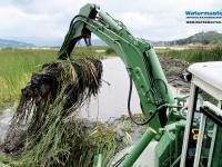 Watermaster dredger removing invasive vegetation from a lake by raking